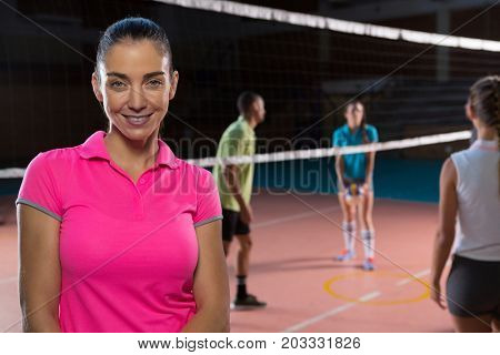 Portrait of smiling female volleyball player by teammates at court