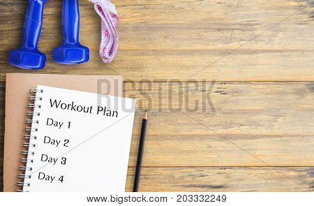 Flat lay - Blue dumbbell Measuring Tape Pencil and health clipboard indicating workout plan on wooden table. Top view with copy space for any design. Healthy and fitness concept.
