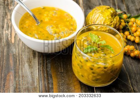 Passion fruit juice in a glass and a bowl with spoon for eating on wooden background,healthy fruit