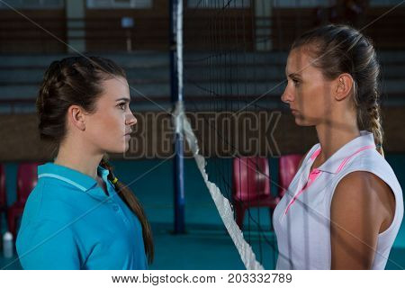 Aggressive female volleyball players looking each other through net at court