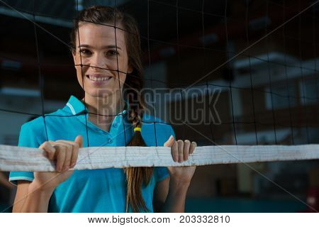 Portrait of happy female volleyball player standing behind net at court