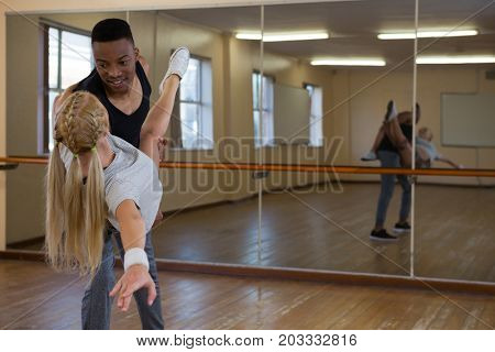 Dancers looking each other by mirror at dance studio