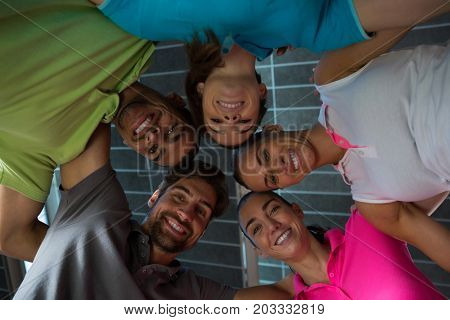 Low angle portrait of smiling volleyball players huddling at court