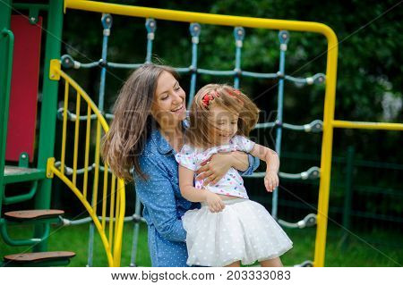 Young mother plays in the playground with the little daughter. Woman holds on hands child. To mother and the daughter it is very cheerful.. Sunny summer day. Good mood.