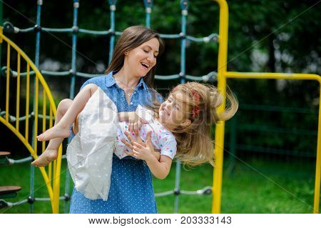 Young mother plays in the playground with the little daughter. Woman holds on hands child. Baby has barefoot legs and hair disheveled from a game. Sunny summer day. Good mood.