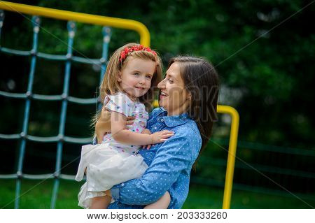 The young woman holds the little daughter on hands. Mother gently embraces the child.