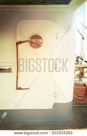 Big sailboat metal door with a round window