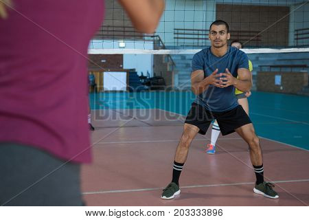 Full length of male player playing volleyball at court