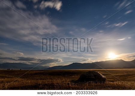 Beautiful night landscape with a big stone in the steppe moonrise stars and clouds in the night sky against the background of the mountains