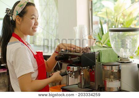 Asian woman barista preparing coffee in the coffee shop