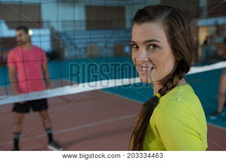 Portrait of smiling female volleyball player with braided hair at court