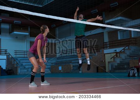 Full length of woman looking at male teammate jumping at volleyball court
