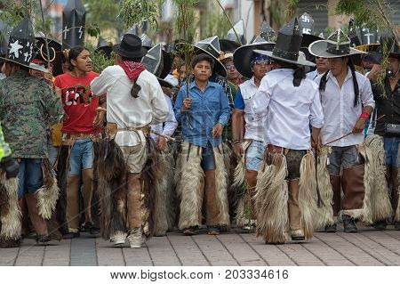 June 29 2017 Cotacachi Ecuador: indigenous kichwa men with extra large sombreros and leather chaps at Inti Raymi celebration