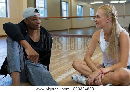 Young friends talking while relaxing on floor in dance studio