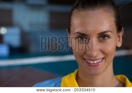 Close-up portrait of smiling female volleyball player at court