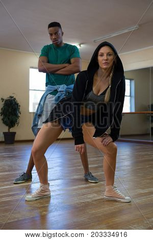 Full length of young female dancer with friend rehearsing on floor in studio