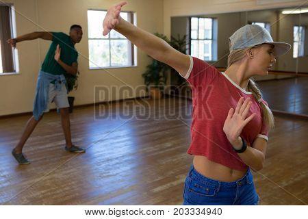 Young friends practicing dance on wooden floor in studio