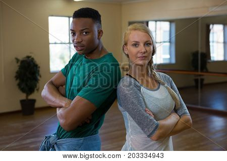 Portrait of confident dancers standing on floor in studio