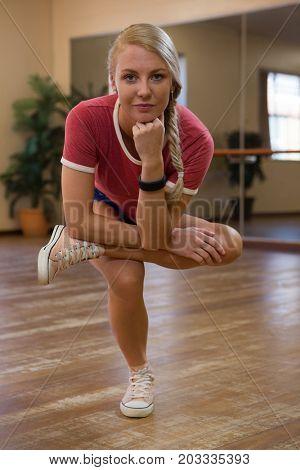 Full length portrait of female dancer practicing on wooden floor in studio