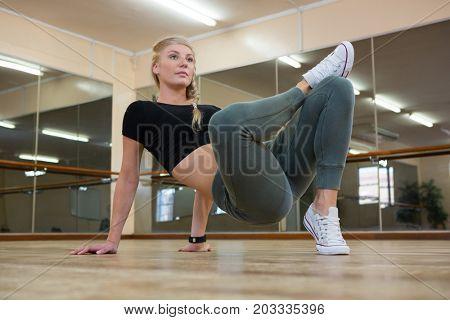 Full length of female dancer practicing on wooden floor in illuminated studio