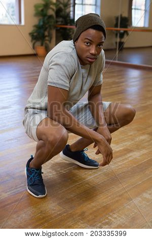 Full length portrait of male dancer crouching on wooden floor in studio