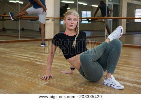 Full length portrait of woman practicing dance on hardwood floor in studio