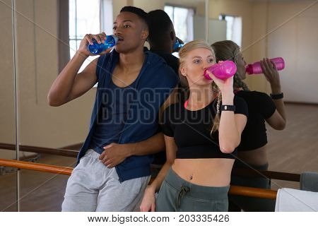 Tired young dancers looking away while drinking water in studio
