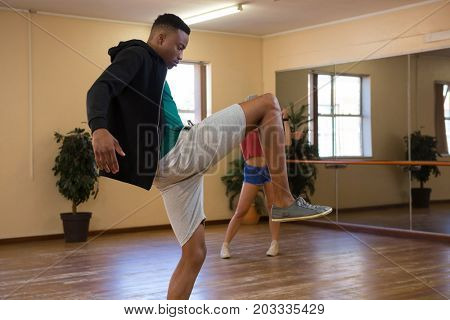 Side view of young male dancer practicing on wooden floor in studio
