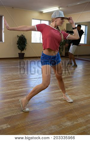 Full length of female dancer with friend rehearsing on wooden floor in studio