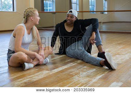 Full length of dancers talking on wooden floor in studio