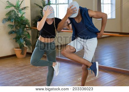 Young friends rehearsing dance by mirror in studio