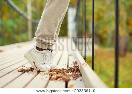 Woman feet in white shoes standing tiptoe on hanging bridge in autumn park. Side view. Outdoors fall season multicolored horizontal image.
