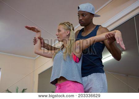 Man assisting female dancer in stretching at dance studio