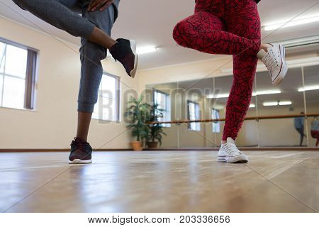 Low section of young friends rehearsing dance on hardwood floor in studio