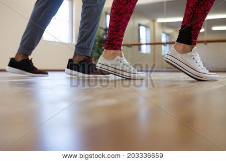Low section of woman with friend rehearsing dance on wooden floor in studio