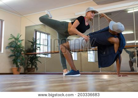 Full length of friends rehearsing dance on floor in studio