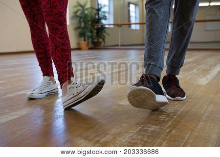 Low section of man with friend practicing dance on floor in studio