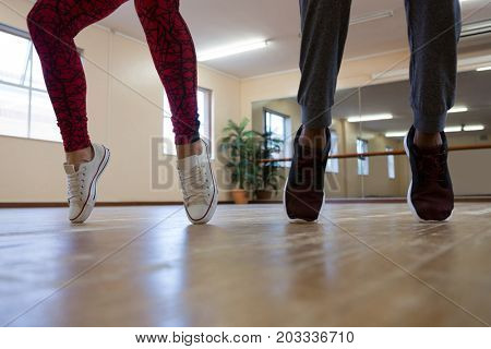 Low section of woman with friend practicing dance on floor in studio