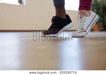 Low section of friends dancing on wooden floor in studio