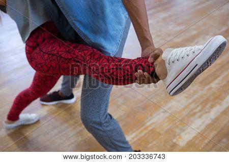 Low section of friends practicing dance on hardwood floor in studio