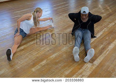 Young friends dancing on hardwood floor in studio