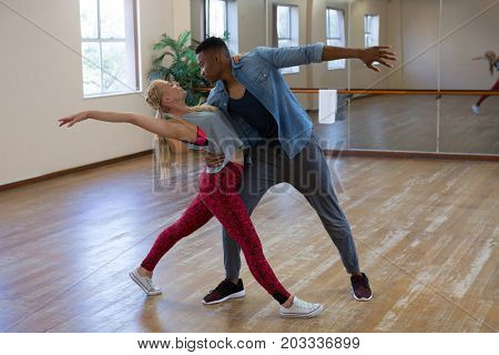Full length of young friends dancing in studio