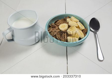 Wheat flakes and banana slice in bowl with milk jug on table