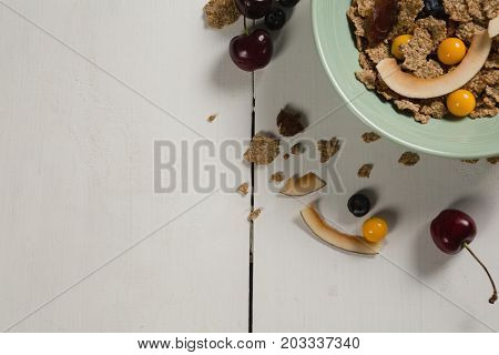 Bowl of wheat flakes with blueberry and golden berry on table
