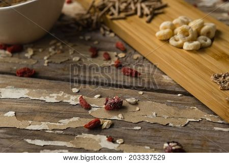 Close-up of breakfast cereals and dry fruits on wooden table