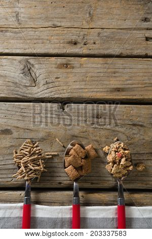 Three spoons with various breakfast cereals on wooden table