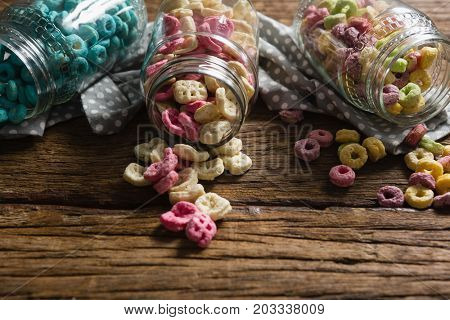 Close-up of scattered honeycomb cereals from jar on wooden table