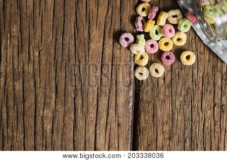 Overhead view of scattered cereal rings from jar on wooden table