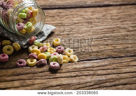 Close-up of scattered cereal rings from jar on wooden table
