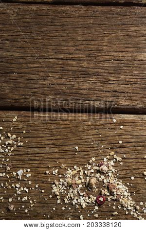 Close-up of scattered dry fruits and breakfast cereals on wooden table